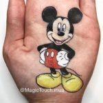 Personajes de disney dibujados en la palma de la mano